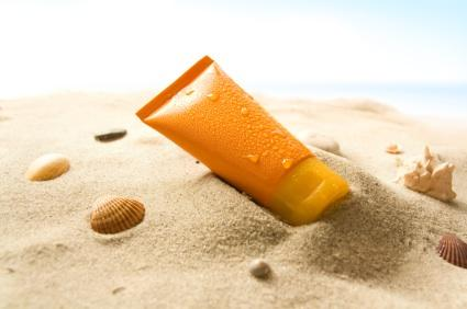 image of an orange plastic container of sunscreen on a pile of sand