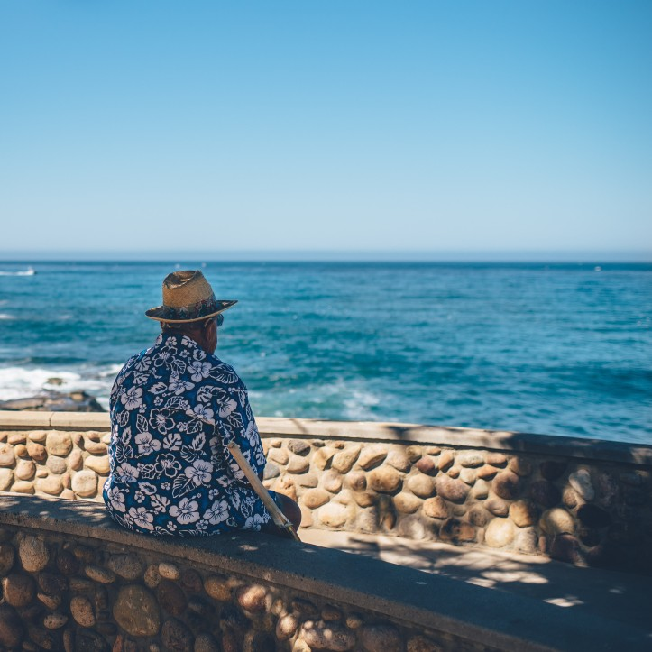 photo of older man wearing a hat and looking out to sea