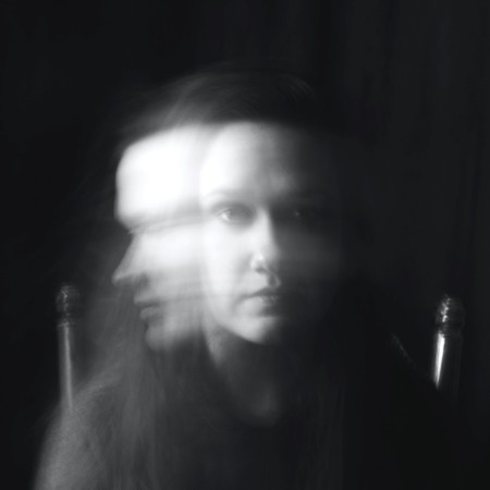 shadow photo of young woman looking serious trapped in the past