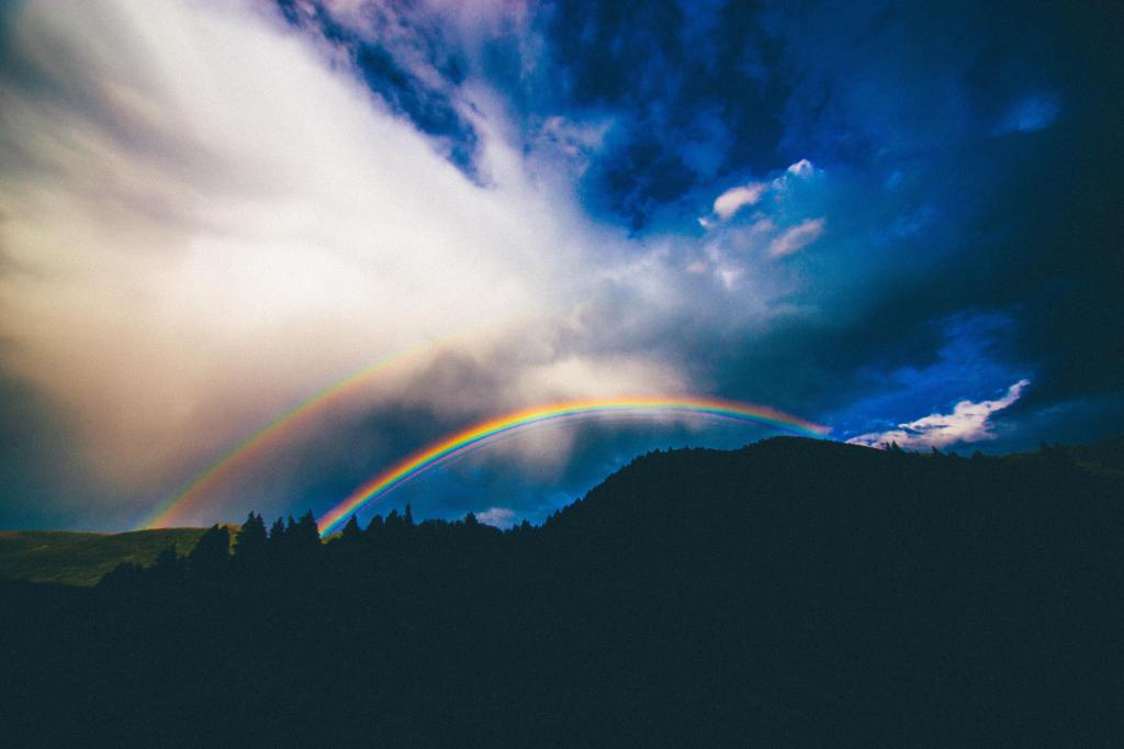 Photo of a double rainbow against a dark blue sky and the silhouette of mountains and trees.