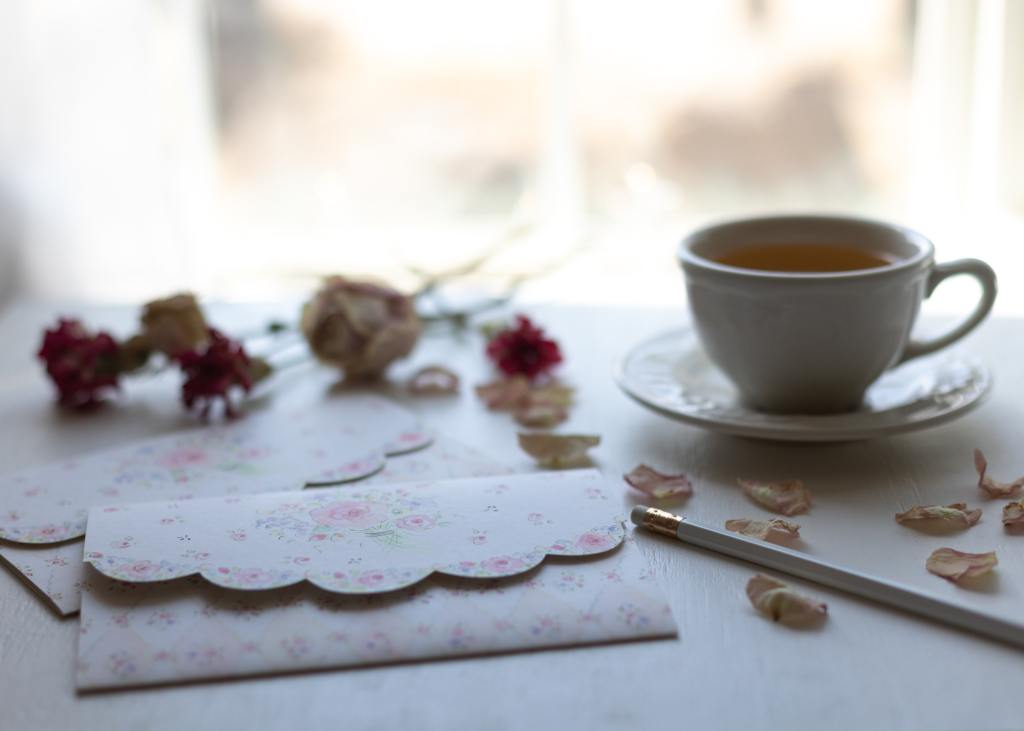 image of a tabletop with a cup of tea, some stationary, a pencil, and some dried roses