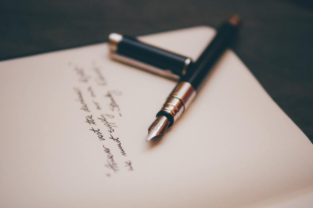 Image of a piece of paper with some cursive writing on it and a fountain pen lying on top of the paper.