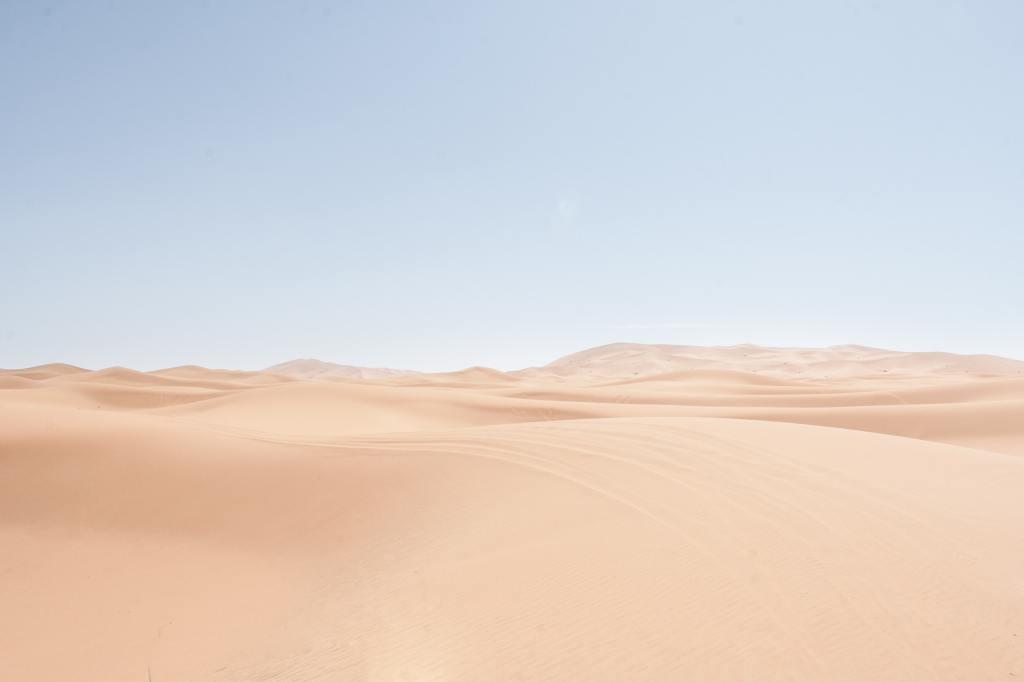 image of desert sand against a blue sky